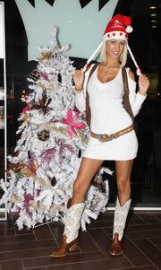 Τέσσερις κούκλες σε ρόλο Άη Βασίλη δίπλα στο christmas tree
