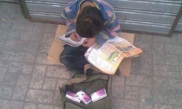 Απίστευτη φωτογραφία: Παιδάκι πουλάει χαρτομάντιλα και μελετάει!