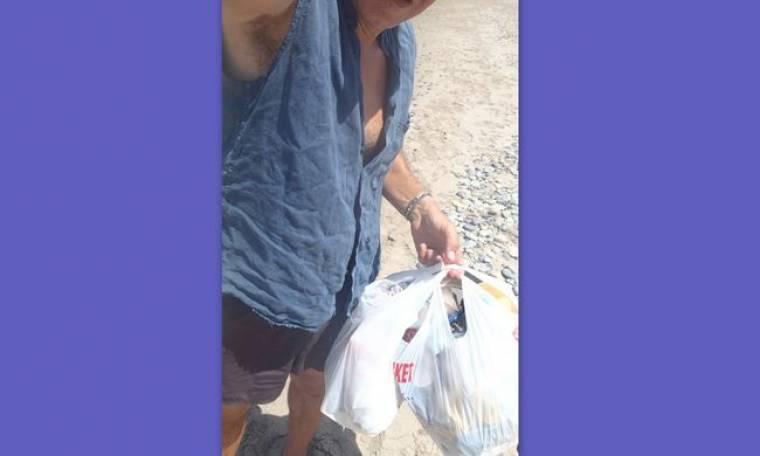 Χύνει ιδρώτα μαζεύοντας τα σκουπίδια στην παραλία (φωτό)