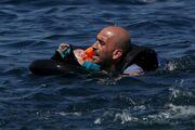 Συγκλονιστική φωτογραφία: Πρόσφυγας με μωρό στην αγκαλιά κολυμπάει προς τη Λέσβο